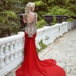 Fashion elegant blond woman model in red gown with long train of — Stock Photo #74054427