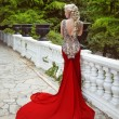 Fashion elegant blond woman model in red gown with long train of — Stock Photo #74054461