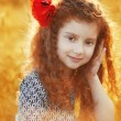 Beautiful smiling little girl with curly hair in the grass field — Stock Photo #75895929