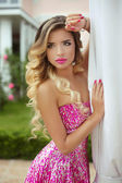 Beauty blond model girl in fashion pink dress with makeup and lo — Stock Photo