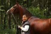 äldre kvinna och bruna hästen stående i skogen — Stockfoto