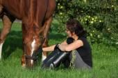 Женщина и лошадь, покоящаяся при задевании — Стоковое фото