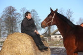 Teenager boy resting on the hay bale and bay horse — Stock Photo