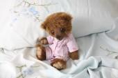Cute teddy bear in pink pyjama — Stock Photo