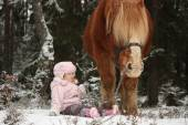 Small girl sitting in the snow and big palomino horse standing n — Stock Photo