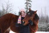 Beautiful teenager girl hugging brown horse in winter — Stock Photo