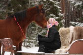Teenager girl sitting in the sled with furs and brown horse — Stock Photo