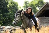 Portrait of beautiful woman on horse near the barn — Foto Stock