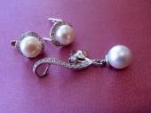 Earrings and pendent with sea pearls and cubic zirconias on a pink background close up. — Stock Photo