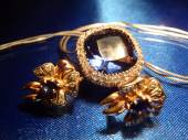Gold earrings and pendent with sapphires on blue macro — Stock Photo