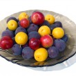 Multi-colored plums in a plate close up. — Stock Photo #66651457