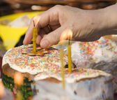 Hand lightes up candle on Easter cakes — ストック写真