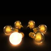 One Bright bulb amoung Six Incandescent Lightbulbs in a circle o — Stock Photo