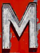 "Vintage, run-down, antique letter ""M"" on a red background — Foto de Stock"