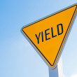 A yellow yield sign against a blue sky background — Stock Photo #66105115