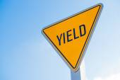 A yellow yield sign against a blue sky background — Stock Photo