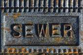 Sewer access cover with rusty iron — Stock Photo