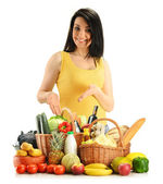 Young woman with groceries in wicker basket isolated on white — Stock Photo