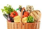 Groceries in wicker basket isolated on white — Stock Photo