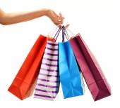 Female hand holding paper shopping bags isolated on white — Stock Photo