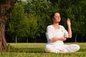 Young woman during yoga meditation in the park — Stock Photo