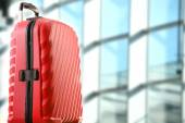 Red plastic travel suitcase in the airport hall — Stock Photo
