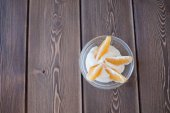 Yogurt and orange slices in a glass dish on a wooden table — Stock Photo