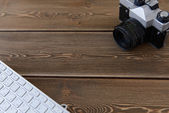 Camera and keyboard on a dark desk background — Stock Photo