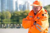 Positive caucasian man worker at city buildings background — Стоковое фото