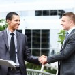 Two cheerful businessman handshaking in conference hall — Stock Photo #55562867