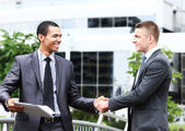 Two cheerful businessman handshaking in conference hall — Stockfoto