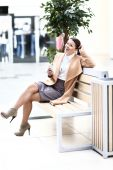 Full length of young woman with phone sitting in shopping centre — Stock Photo