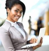 Smiling african businesswoman with laptop computer — Stock Photo