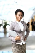 Smiling young african businesswoman with briefcase — Stock Photo