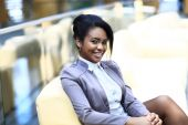 Portrait of smiling young businesswoman sitting at computer  in office — Stock Photo