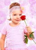 People, happiness concept. Happy little girl with rose in pink clothes — Stock Photo
