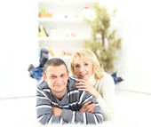 Cheerful couple laying on the floor at home — Stock Photo