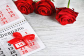 Red roses lay on the calendar with the date of February 14 Valentine's day — Stock Photo
