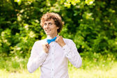 Curly man in white shirt and blue bow tie smiling — Stock Photo