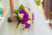 Bride holding violet wedding carnation bouquet against gown — Stock Photo