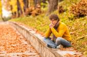 Sad curly man siting outdoor — Stock Photo