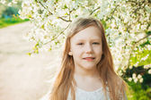 Little girl in a white dress on a sunny spring garden — Stock Photo