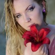 Beautiful blonde in water with flower — Stock Photo #68349971