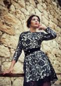 Young beautiful girl posing near a stone wall — Foto Stock