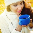Young beautiful girl drinking a hot drink in the park — Stock Photo #59693131