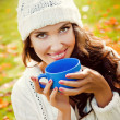 Young beautiful girl drinking a hot drink in the park — Stock Photo #59693133