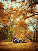 Young couple sitting embracing nature — Stok fotoğraf