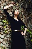 Fashionable young woman posing near a stone wall — Stock Photo
