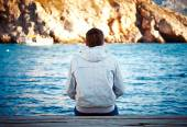 Lonely young man sitting on the dock — Stock Photo