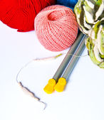 Several multi-colored balls of yarn and knitting needles — Stock Photo